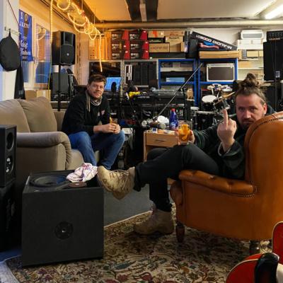 Zwei Personen, die auf Stühlen sitzen und sich zur Kamera hindrehen