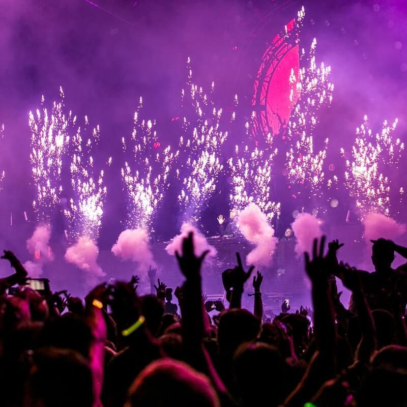 Szene auf einer Party, mit Feuerwerk, Rauch und Händen in der Luft