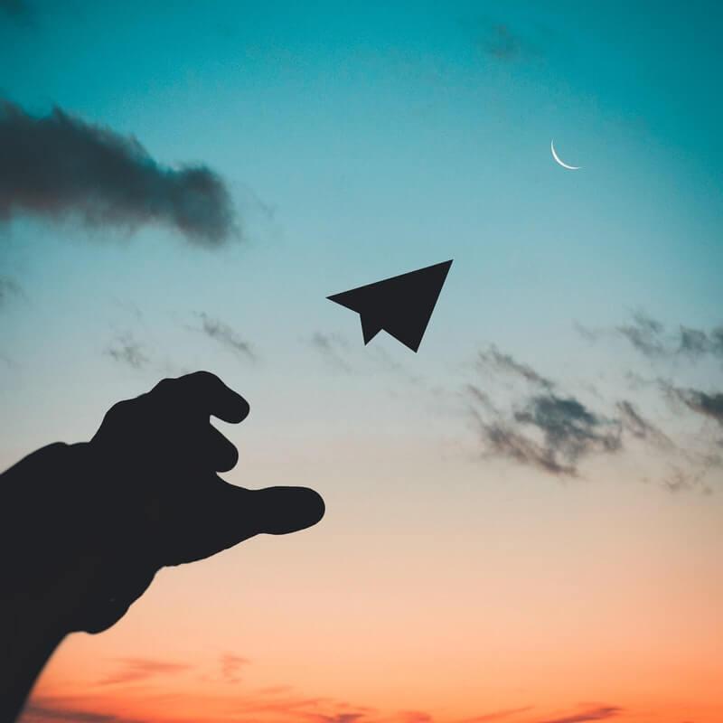 Hand, die Papierflieger wirft vor einem Sonnenuntergang