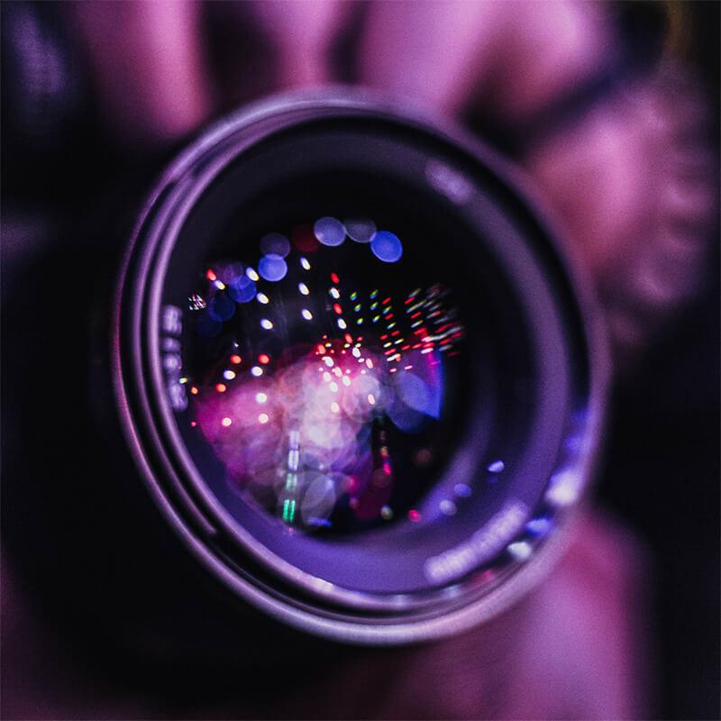 Nahaufnahme einer Kameralinse, in der sich Lichter reflektieren
